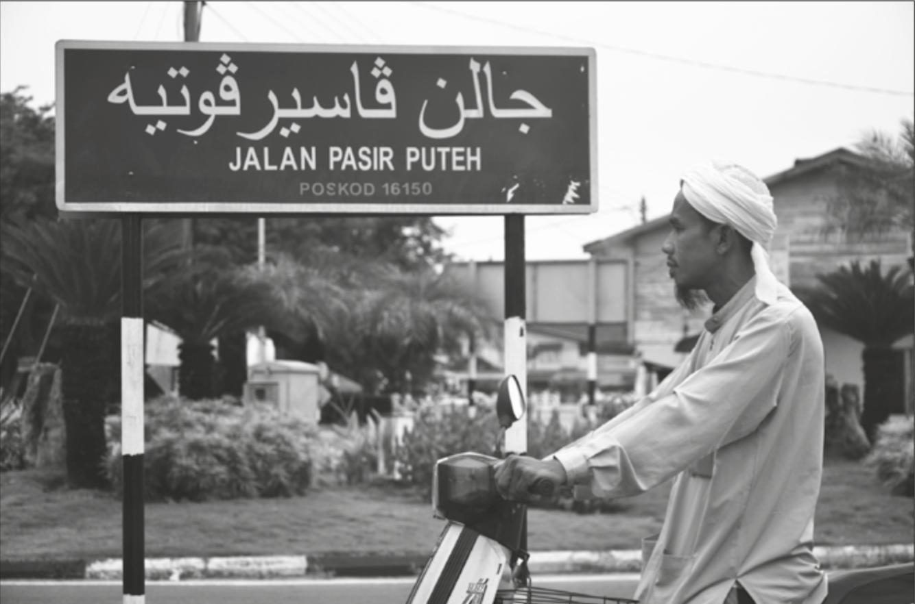 Un panneau indiquant le nom d'une rue en Indonésie en alphabet adjami et en alphabet latin.